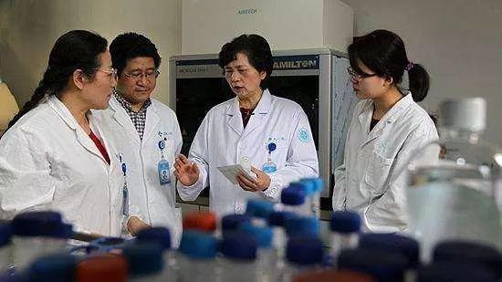 ・李兰娟(右二)和同事们一起研究问题。