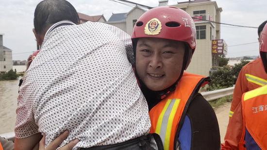 余雷欢在搜救中,抱起一名残疾男子撤离。受访者供图