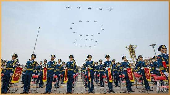 """△29架直升机组成""""100""""字样掠过长空。(总台记者廖江衡拍摄)"""
