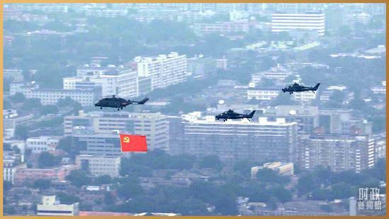 △直升机悬挂鲜红的中国共产党党旗飞过。