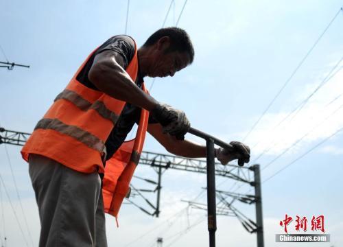 資料圖:南昌鐵路局九江橋工段的工人們在京九鐵路九江區段頂著高溫更換傷損鋼軌。 胡國林 攝