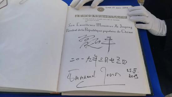 △习近平和马克龙在贵宾簿上签字。(央视记者李铮拍摄)