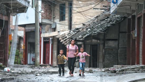 ▲昨日,四川省长宁县双河镇,一位母亲领着两个孩子准备去临时安置点休息。 新京报记者 彭子洋 摄