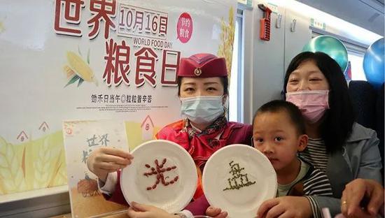 2020年10月15日,在重庆北开往万州北的C6404次列车上,乘务员向乘客宣讲拒绝餐饮浪费等知识。图片来源:人民视觉
