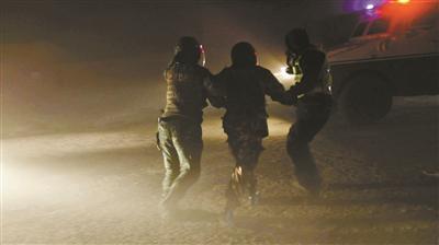 武警官兵帮被困者戴上头盔,在飞沙走石中将其引导至装甲车旁 供图/武警新疆总队克拉玛依支队