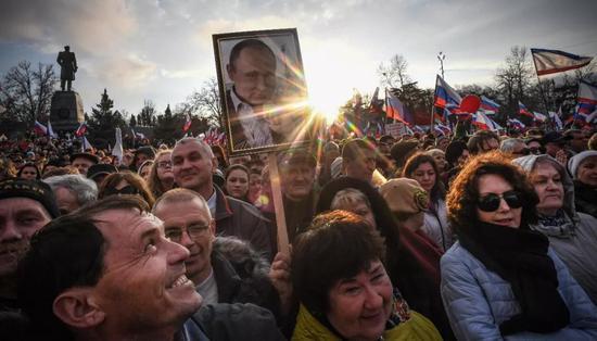△2018年俄罗斯大选前的竞选运动,俄罗斯民多高举普京照片。