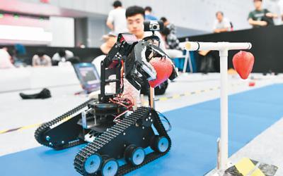 10月25日,在广东佛山举行的第二十届中国机器人及人工智能大赛上,一位选手操作智能农业机器人参加采摘比赛。新华社记者 沙达提摄