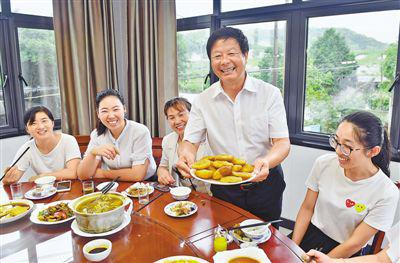 正在上菜的黄彭勋(右二)热情地向客人介绍农家乐传统手工特色菜——油盐麦果。陈斌荣摄