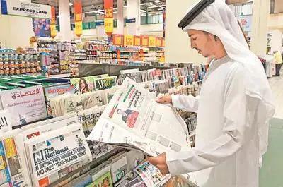 △7月18日,在阿联酋阿布扎比购物中心的报纸售卖区,当地读者打开《联邦报》,阅读习近平的署名文章
