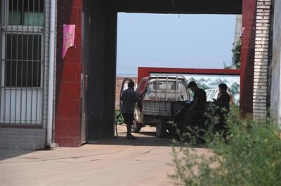 """定州X358县道旁,一家标有""""冀保网F050""""的加油站在后院给车辆加油。"""