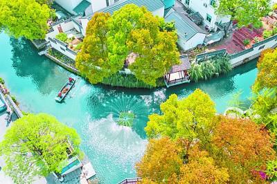 浙江省长兴县龙山街道渚山村的保洁人员乘船修整河面漂浮物。新华社发