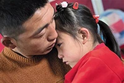 ▲大女儿在一旁落泪,曹永平把孩子揽在怀里,泣不成声。