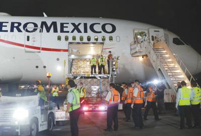 4月7日晚,墨西哥政府从中国采购的首批防疫医疗物资运抵墨西哥城国际机场。图为墨方工作人员正在卸载相关物资。新华社发