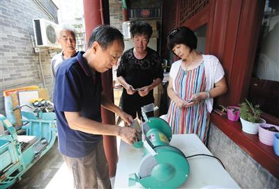 7月29日,兴隆都市馨园社区,王来平正在为社区居民磨刀。