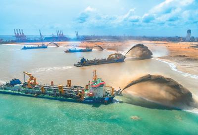 资料图:斯里兰卡科伦坡,来自中国的四条大型耙吸挖泥船同时在吹沙(图源:新华社)