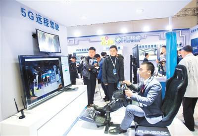 """11月14日,在第十五届""""中国光谷""""国际光电子博览会上,观众在中国移动展区体验5G远程驾驶。新华社记者 熊 琦摄"""