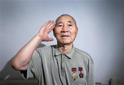 7月28日,东花市街道,96岁王登旺戴着奖章敬礼。