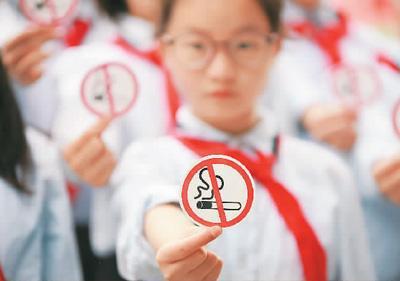 江苏省扬州市维扬实验小学北区校的学生展示禁烟标志。 孟德龙摄(人民视觉)