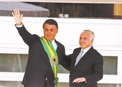 1月1日,巴西总统雅伊尔·博索纳罗(左)从卸任总统特梅尔手中接过象征总统权力的绶带 供图/新华社