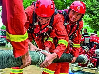 江苏南京消防救援队伍利用龙吸水和移动供水泵组对积水区域进行抽水排涝。应急管理部消防救援局供图