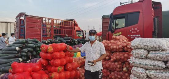 在新发地批发市场临时交易区,经营户正在盘点货品。受访者供图