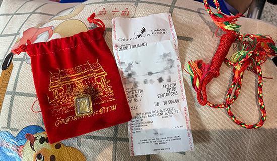 """该游客购于泰国芭提雅金龙寺的""""佛牌""""及购买收据。 受访者 供图"""
