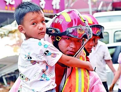 7月21日,在巩义市米河镇,消防救援人员帮助群众转移。新华社发