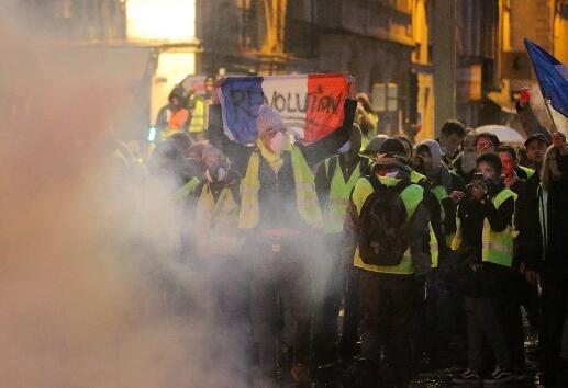 """示威者挥舞的法国国旗上写着""""革命""""(图源:视觉中国)"""