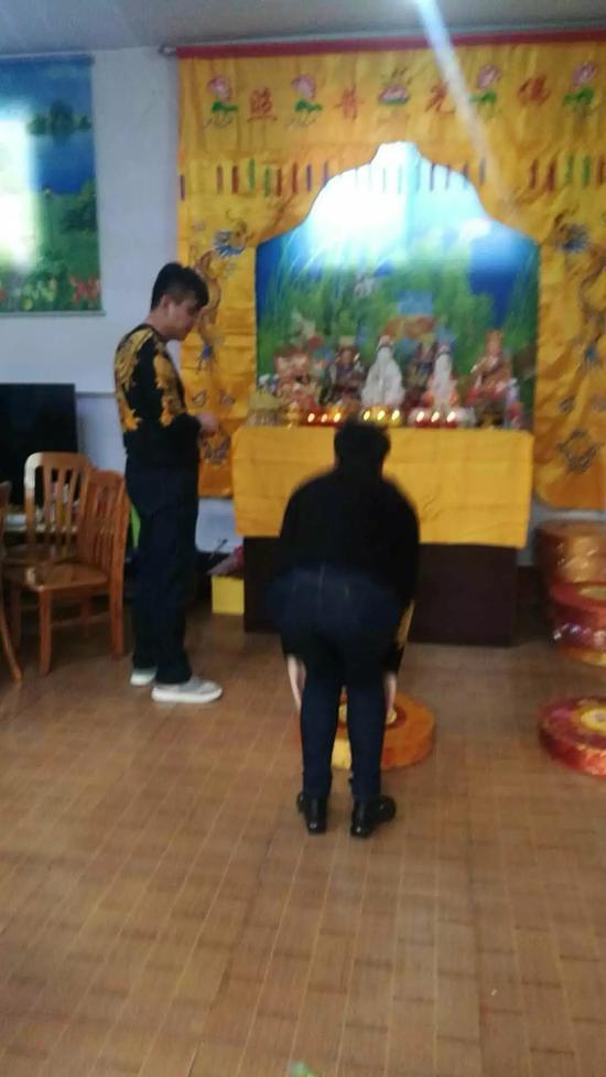 周文登(图左)让人们跪拜神像。受访者供图