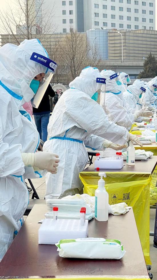 1月22日,在北京 西城区展览馆前广场的核酸采样点,医务人员为采集核酸样本做准备。