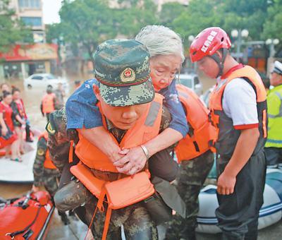 8月11日,浙江临海,武警救援人员将一位受困老人转移到安全地区。影像中国