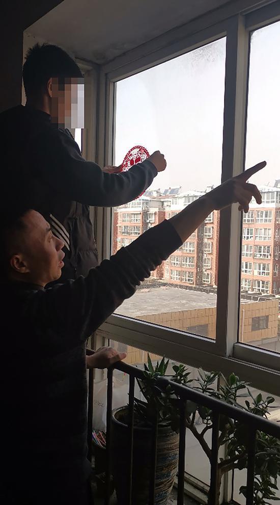 """2021年春节前,申军良在家里指挥申聪贴""""福""""字。 受访者 供图"""