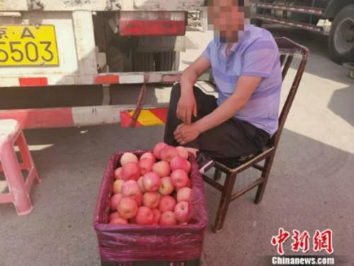 图为新发地卖苹果的摊贩。 谢艺观 摄