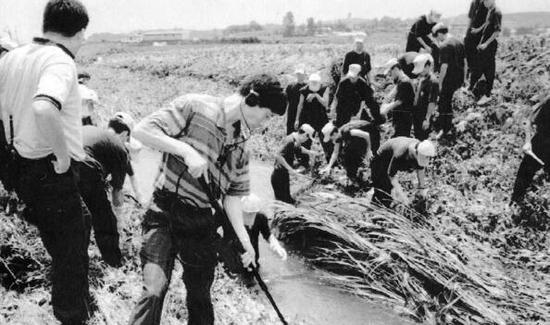 1993年7月,韩国警方在华城郡正南面观项里一带寻找华城连环杀人案的现场遗留物。(图源:韩联社)
