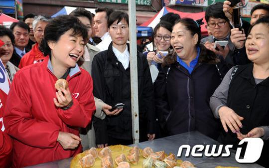 2012年3月,朴槿惠在传统市场包子摊前,与商贩开心交谈。(News 1)