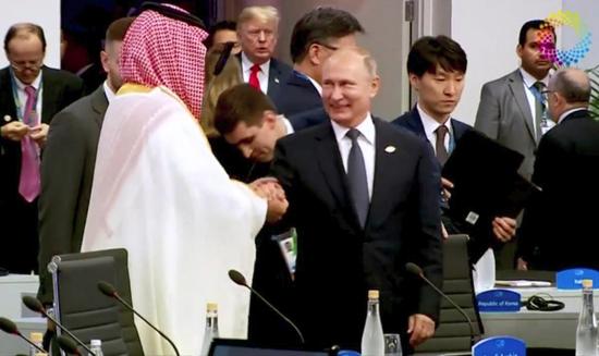 普京在G20峰会上与沙特阿拉伯王储握手。(路透社)