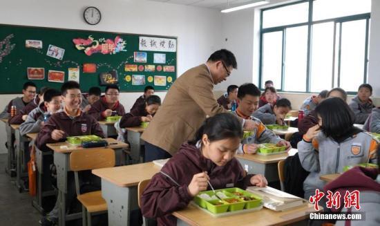 资料图为:南京钟英中学的校长走进教室与学生一起吃中饭。葛勇 摄