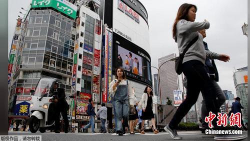 原料图片:2017年5月17日,日本东京新宿商业区,人们穿过街道。