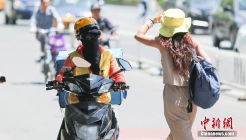 5月23日,外賣小哥在高溫晴曬環境下工作。中新社記者 賈天勇 攝