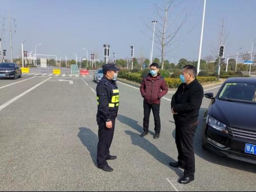 刘勋(中间)在江夏区高速路口巡查武汉出城道路封控情况