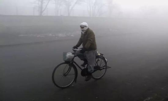 一名男子在雾霾笼罩的阿富汗首都喀布尔骑行。新华社发