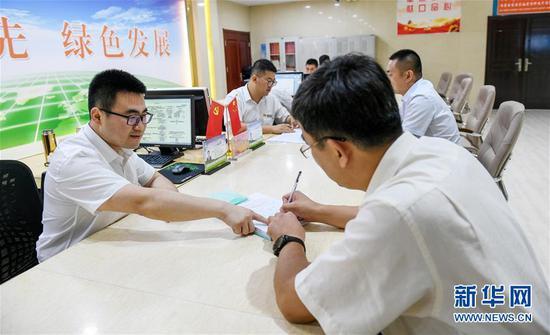 7月16日,在内蒙古自治区自然资源厅的自然资源政务大厅内,办事员(左)为采矿企业办理相关审批手续。新华社记者 彭源 摄