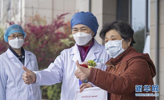 在武汉大学人民医院东院区,李兰娟(中)与出院患者合影(3月16日摄)。 新华社记者 才扬 摄