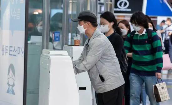 戴口罩的乘客们在首尔车站内进走消毒。新华社图
