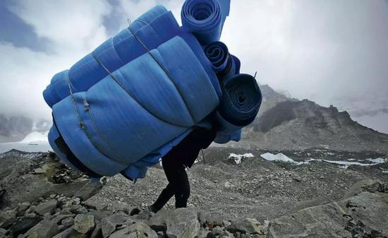 别名夏尔巴人背着大堆睡垫从珠峰大本营返回。图/ 视觉中国