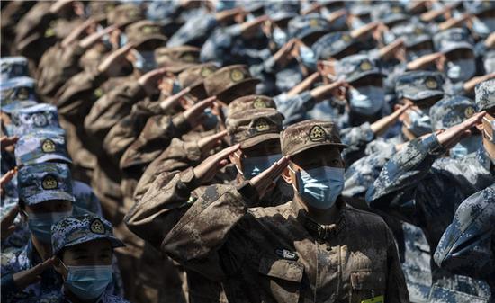 4月15日,最后一批回撤的军队支援湖北医疗队队员向火神山医院敬礼告别。新华社记者 费茂华 摄