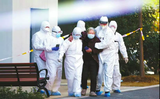 民警史雪荣(右二)与医务工作者一起转运疑似患新冠肺炎老人