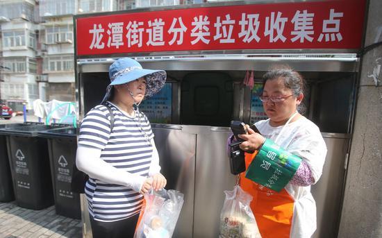 2019年7月8日,东城区龙潭街道清明楼幼区,一位垃圾分类请示员为居民分益类的厨余垃圾称重积分。摄影/新京报记者 王贵彬