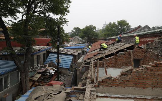 施工工人在拆除房屋屋顶砖瓦。摄影/新京报记者 侯少卿