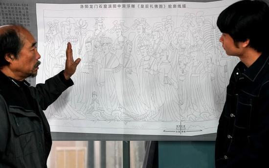西安交通大学教授贾濯非(左)在研究依据老照片和残壁数字模型同坐标合成后提取的浮雕构图轮廓线(4月8日摄)。新华社记者李安摄